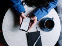 Una mujer escribe un comentario en una Red Social desde su móvil.
